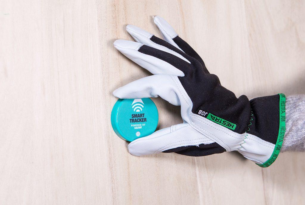 Henkilö työhanska kädessä pitää kädessä sinistä Smart Trackeria.